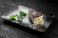 Foto des Kuchens mit Nüssen und tadellosem Blatt auf dem schwarzen hölzernen Hintergrund Stockfotografie