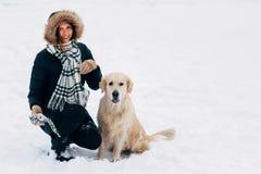 Foto des lächelnden Mädchens mit Hund im Winterpark Stockfoto