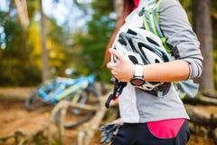 Foto des Mädchens mit dem Sturzhelm, der auf Hintergrund des Fahrrades steht Lizenzfreie Stockbilder