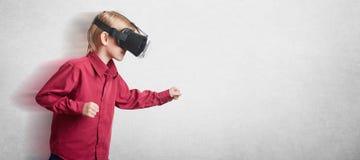 Foto des männlichen Kindes benutzt oculus Risskopfhörer, schaut froh, gestikuliert aktiv, spielt Spiele, aufwirft gegen weißen Hi Lizenzfreie Stockfotografie