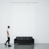Foto des Mannes in der Galerie Leeres Segeltuch Waching, das an der Backsteinmauer und schwarzen generischen am Designsofabetonbo Lizenzfreies Stockfoto