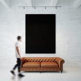 Foto des Mannes in der Galerie Schwarzes leeres Segeltuch Waching, das am Holzfußboden der Backsteinmauer und klassischen des Sof Stockbild