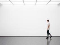 Foto des Mannes in der modernen Galerie, die das leere Segeltuch betrachtet Leeres Modell, Bewegungsunschärfe Stockfoto