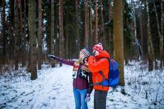 Foto des Mannes mit dem Rucksack und Frau, die Hand vorwärts im Winterwald zeigen Stockbilder