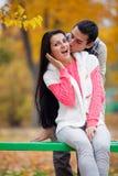 Foto des Mannes seine Frau auf dem wunderbaren Herbstbaum-BAC küssend Lizenzfreies Stockfoto