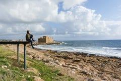 Foto des Mannes sitzend auf Pier an der Küste Lizenzfreie Stockfotos