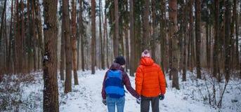 Foto des Mannes und der Frau auf Weg im Winterwald Lizenzfreie Stockfotografie
