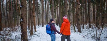 Foto des Mannes und der Frau auf Weg im Winterwald Stockfotografie