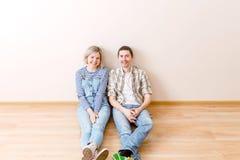 Foto des Mannes und der Frau, die auf Boden sitzen Lizenzfreie Stockfotografie