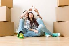 Foto des Mannes und der Frau, die auf Boden unter Pappschachteln sitzen Lizenzfreie Stockbilder