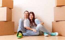 Foto des Mannes und der Frau, die auf Boden unter Pappschachteln sitzen Lizenzfreies Stockbild
