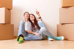 Foto des Mannes und der Frau, die auf Boden unter Pappschachteln sitzen Lizenzfreie Stockfotografie