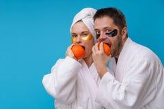 Foto des Mannes und der Frau mit Gelauflagen unter Augen und in schneidenden Orangen der wei?en Robe stockbild