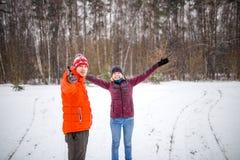 Foto des Mannes und der Frau mit ihren Händen oben im Winterwald Stockbild
