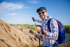 Foto des netten touristischen Mannes mit dem Rucksack, der vorwärts mit Stöcken für das Gehen auf Hügel ausdehnt Stockbild