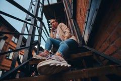 Foto des niedrigen Winkels der unversch?mten Frau in der Sonnenbrille und im Denim am Hinterhof stockfoto