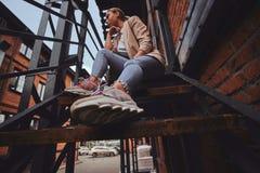 Foto des niedrigen Winkels der unversch?mten Frau in der Sonnenbrille und im Denim am Hinterhof lizenzfreie stockfotografie