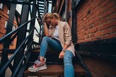 Foto des niedrigen Winkels der unversch?mten Frau in der Sonnenbrille und im Denim am Hinterhof lizenzfreie stockbilder