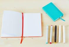 Foto des offenen Sketchbook mit weißem Kopienraum auf hellem Holztisch Mit fünf Markierungen und einem Knickente Sketchbook lizenzfreie stockfotografie