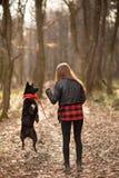 Foto des schönen Mädchens mit ihrem schwarzen Hund im Holz R?ckseitige Ansicht stockfotos