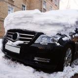 Foto des schwarzen Autos mit Schnee auf Haube an der Straße Lizenzfreie Stockbilder