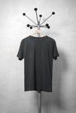 Foto des schwarzen leeren T-Shirts, das am Aufhänger hängt vertikal Lizenzfreies Stockbild