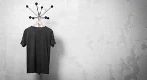 Foto des schwarzen T-Shirts hängend am Aufhänger horizontal Stockbilder