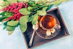 Foto des schwarzen Tees, rote Blumen Lizenzfreies Stockfoto