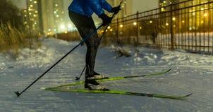 Foto des Skifahrers im Park im Hintergrund des Hauses, brennende Lichter Stockfoto