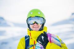 Foto des sportiven Mannes mit Snowboard gegen Hintergrund von Bergen Lizenzfreie Stockfotos