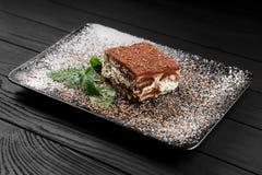 Foto des Tiramisukuchens und Minze treiben auf dem schwarzen hölzernen Hintergrund Blätter Lizenzfreies Stockbild
