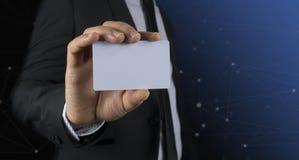Foto des tragenden Anzugs des Geschäftsmannes, der leere Karte auf schwarzem Hintergrund hält Lizenzfreie Stockfotografie