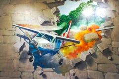 Foto des Wandbilds 3D des fallenden Flugzeuges fuhr aus Steinbacksteinmauer heraus Stockbilder