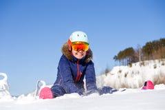 Foto des weiblichen Athleten im Sturzhelm, der an der Schneewehe sitzt Lizenzfreies Stockbild