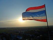 Foto des Wellenartig bewegens der thailändischen Flagge von Thailand mit der Sonne glänzt im Abendhintergrund lizenzfreies stockfoto