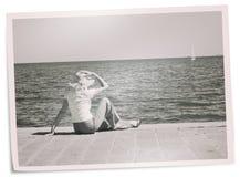Foto descolorada del día de fiesta - la mujer en el muelle mira el yate Fotografía de archivo