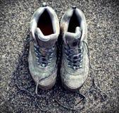 Foto descolorada retra de botas que caminan sucias en la acera imágenes de archivo libres de regalías