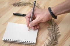 Foto di assorbire la mano maschio del blocco note con il braccialetto fotografia stock