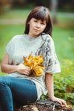 Foto di bella donna abbastanza castana in parco Immagine Stock