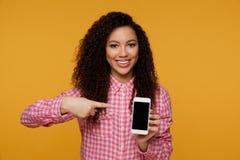 Foto di bella giovane donna sveglia allegra che chiacchiera dal telefono cellulare sopra il fondo giallo della parete osservare fotografia stock