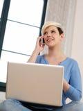 Seduta femminile graziosa con il computer portatile e lo smartphone Fotografie Stock Libere da Diritti