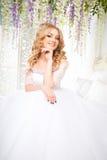 Foto di bella sposa bionda in un vestito da sposa lussuoso nell'interno Immagine Stock