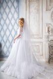 Foto di bella sposa bionda in un vestito da sposa lussuoso nell'interno Fotografie Stock Libere da Diritti