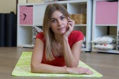 Foto di bello allungamento femminile sul pavimento che si siede su una stuoia Fotografia Stock