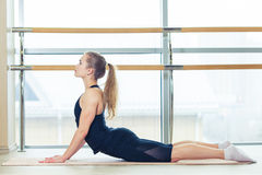 Foto di bello allungamento femminile sulla stuoia di seduta del pavimento Immagini Stock Libere da Diritti