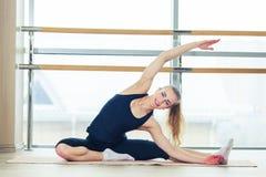 Foto di bello allungamento femminile sulla stuoia di seduta del pavimento Immagini Stock