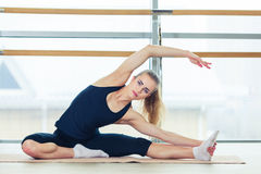 Foto di bello allungamento femminile sulla stuoia di seduta del pavimento Fotografia Stock Libera da Diritti