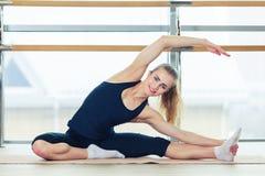 Foto di bello allungamento femminile sulla stuoia di seduta del pavimento Fotografia Stock