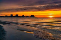 Foto di bello tramonto arancio sul mare, siluetta della città nell'alba sulla spiaggia, paesaggio pacifico, sole giù sopra fotografia stock