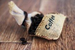 Foto di caffè Insacchi con i chicchi di caffè sul backround di legno Foto dell'alimento Fotografia Stock Libera da Diritti